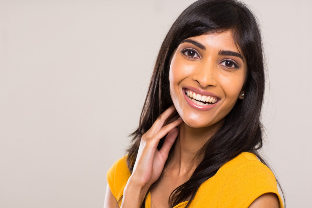 cheerful young indian woman on plain background